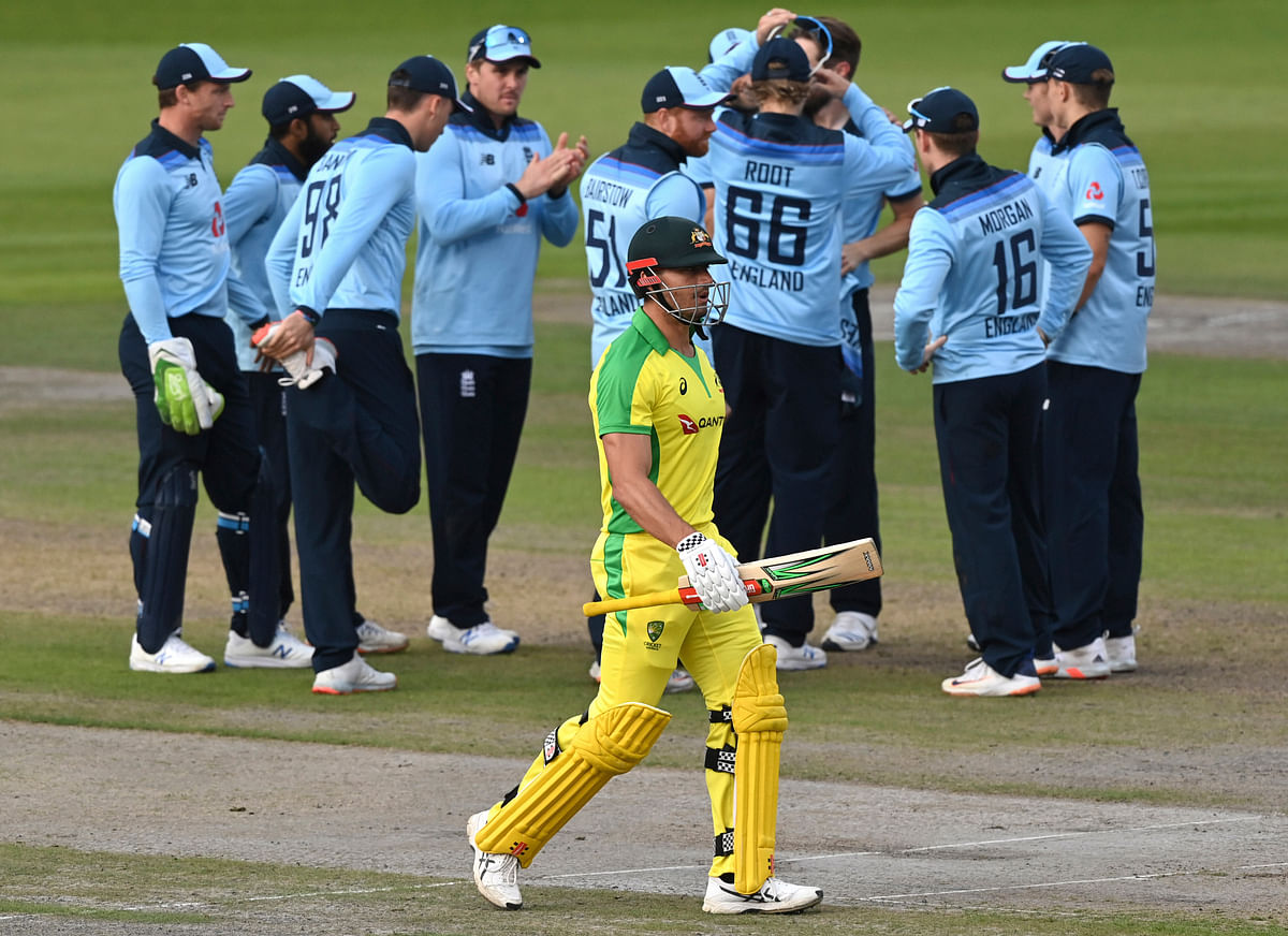 Manchester : Australia's Marcus Stoinis, front, walks off the field after losing his wicket during the third ODI cricket match between England and Australia, at Old Trafford in Manchester, England, Wednesday, Sept. 16, 2020.