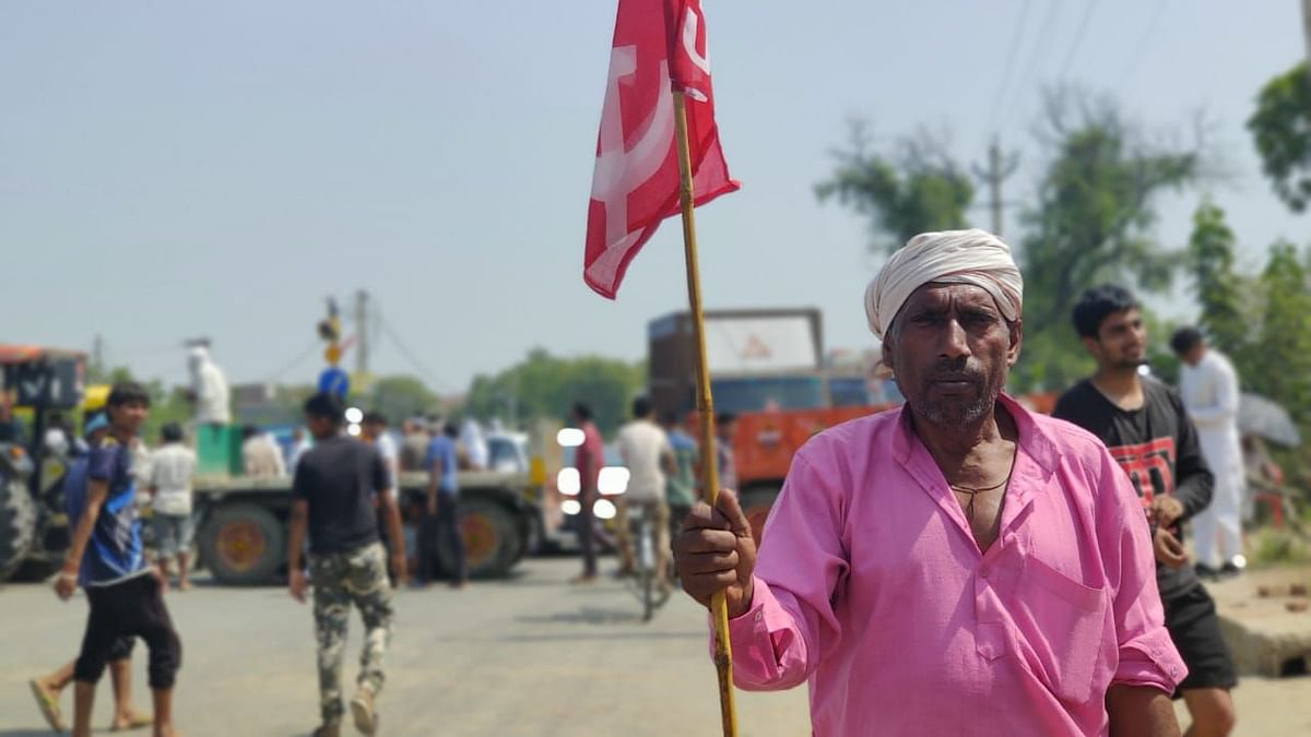 A fermer holds a flag in a protest rally in Haryana's Mahem.