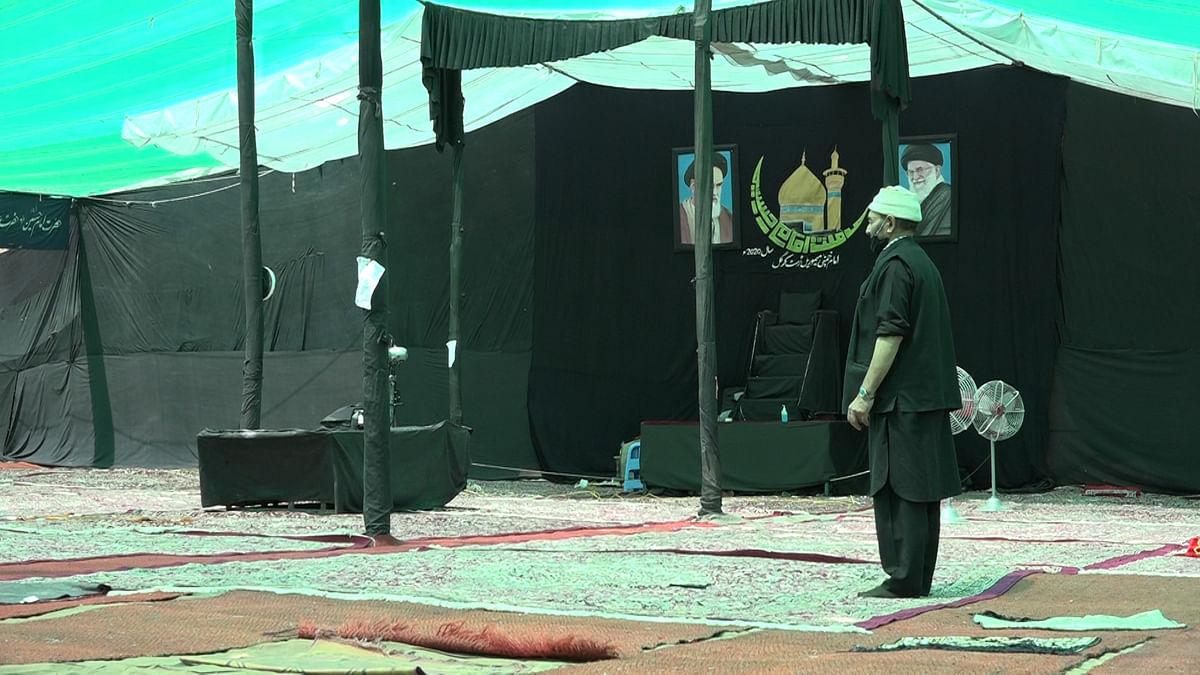 Man offering namaz in majlis hall.