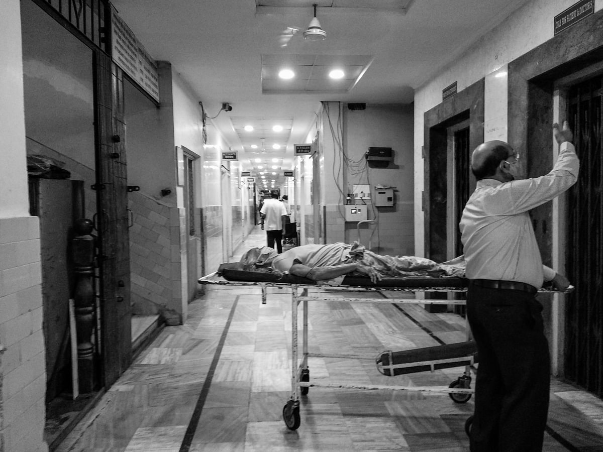 An old man waits for the lift to carry the patient.