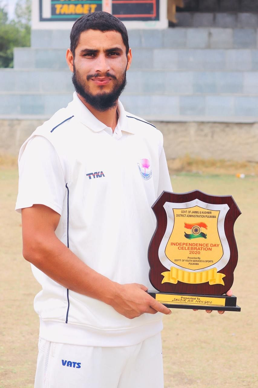 Shabir 'Lefty' posing with the 'Promising Cricketer Award' at Pulwama Stadium