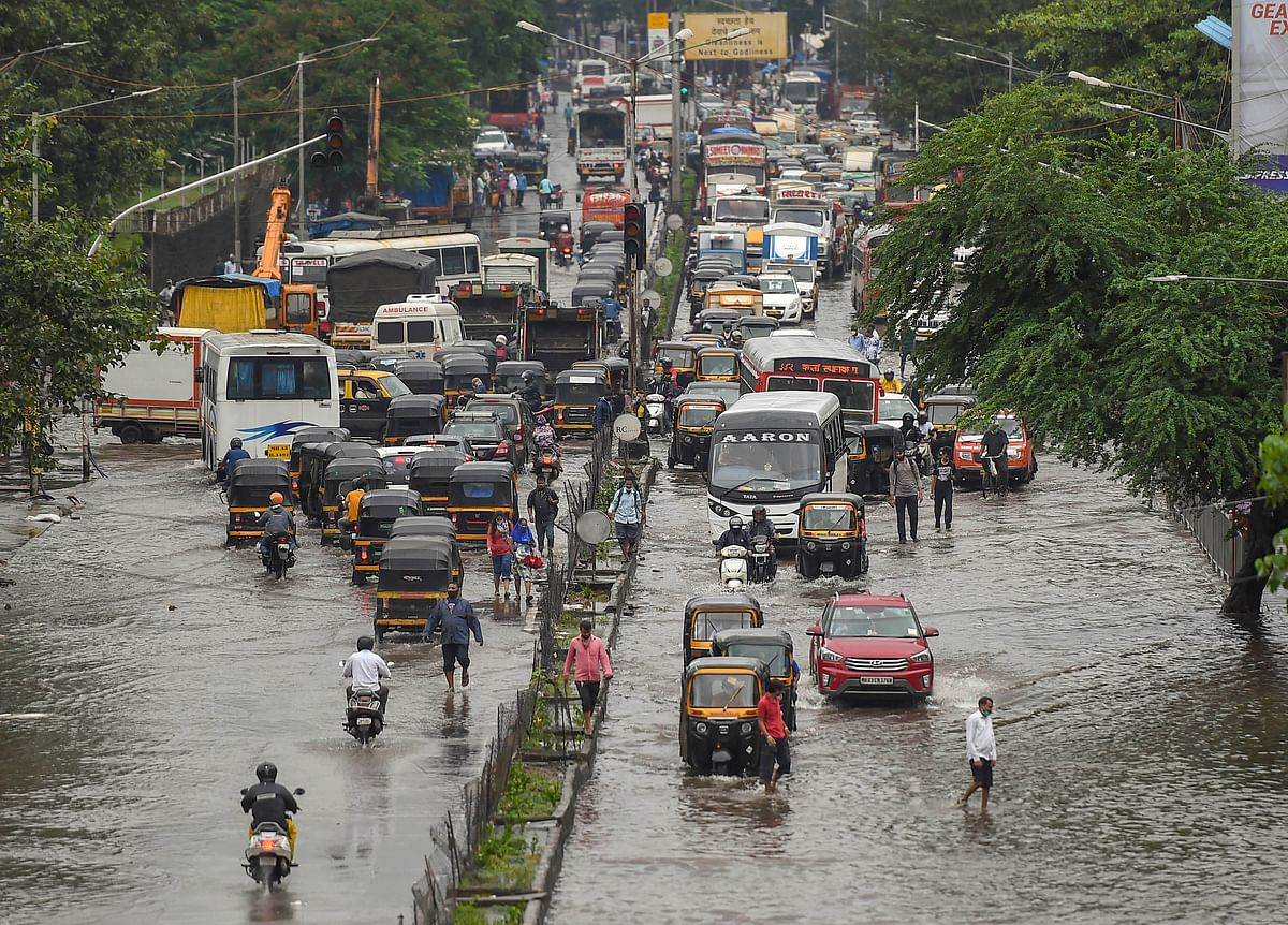 Vehicles move on waterlogged LBS road after heavy monsoon rain, at Kurla in Mumbai, Wednesday, 23 September.