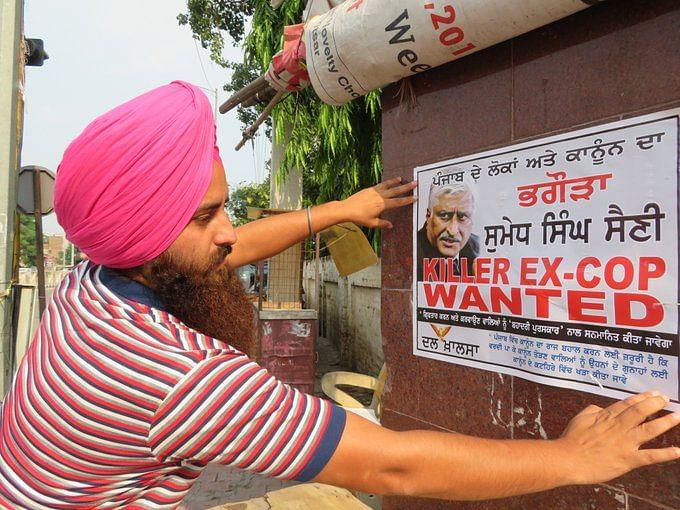 A Dal Khalsa activist puts up a 'wanted' poster of Sumedh Saini.