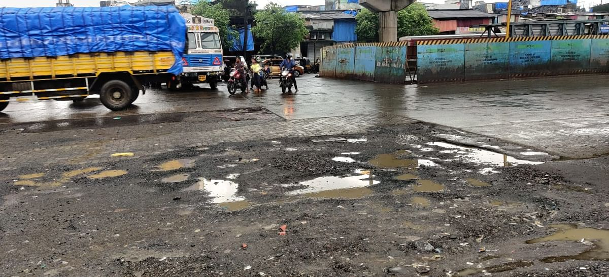 Traffic at the Baiganwadi junction where many potholes can be seen.