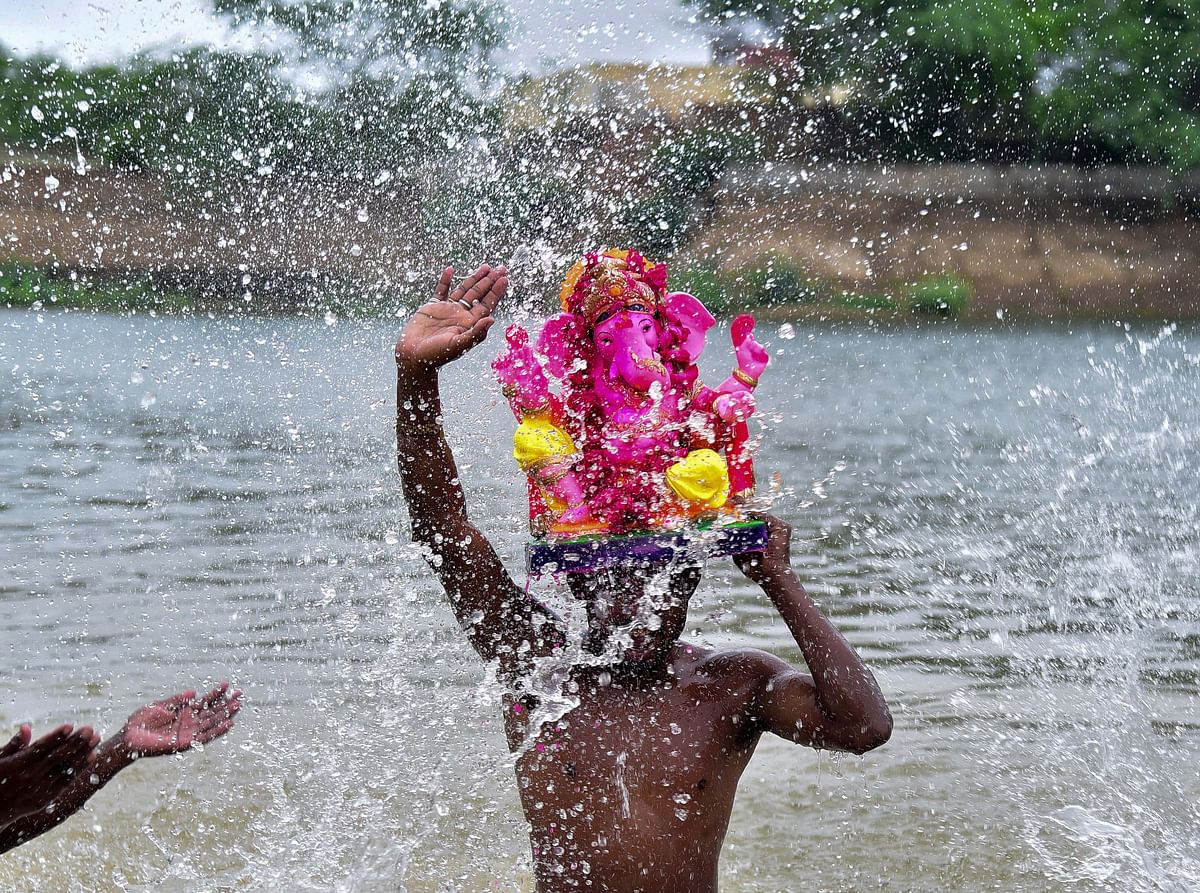 A devotee carries an idol of Lord Ganesh for immersion in the Devi Kund Sagar, during the Ganesh Chaturthi celebrations, at Bikaner.