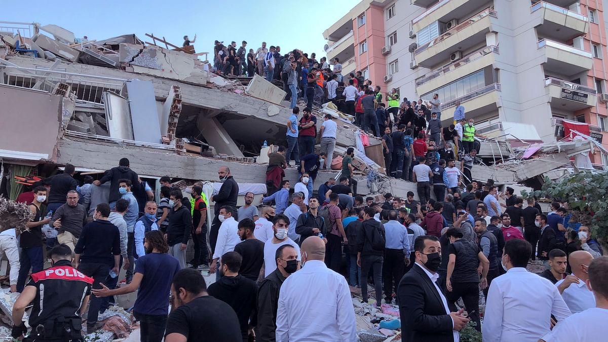 Rescue workers and local people try to reach residents trapped in the debris of a collapsed building, in Izmir, Turkey, Friday, Oct. 30, 2020, after a strong earthquake in the Aegean Sea has shaken Turkey and Greece.