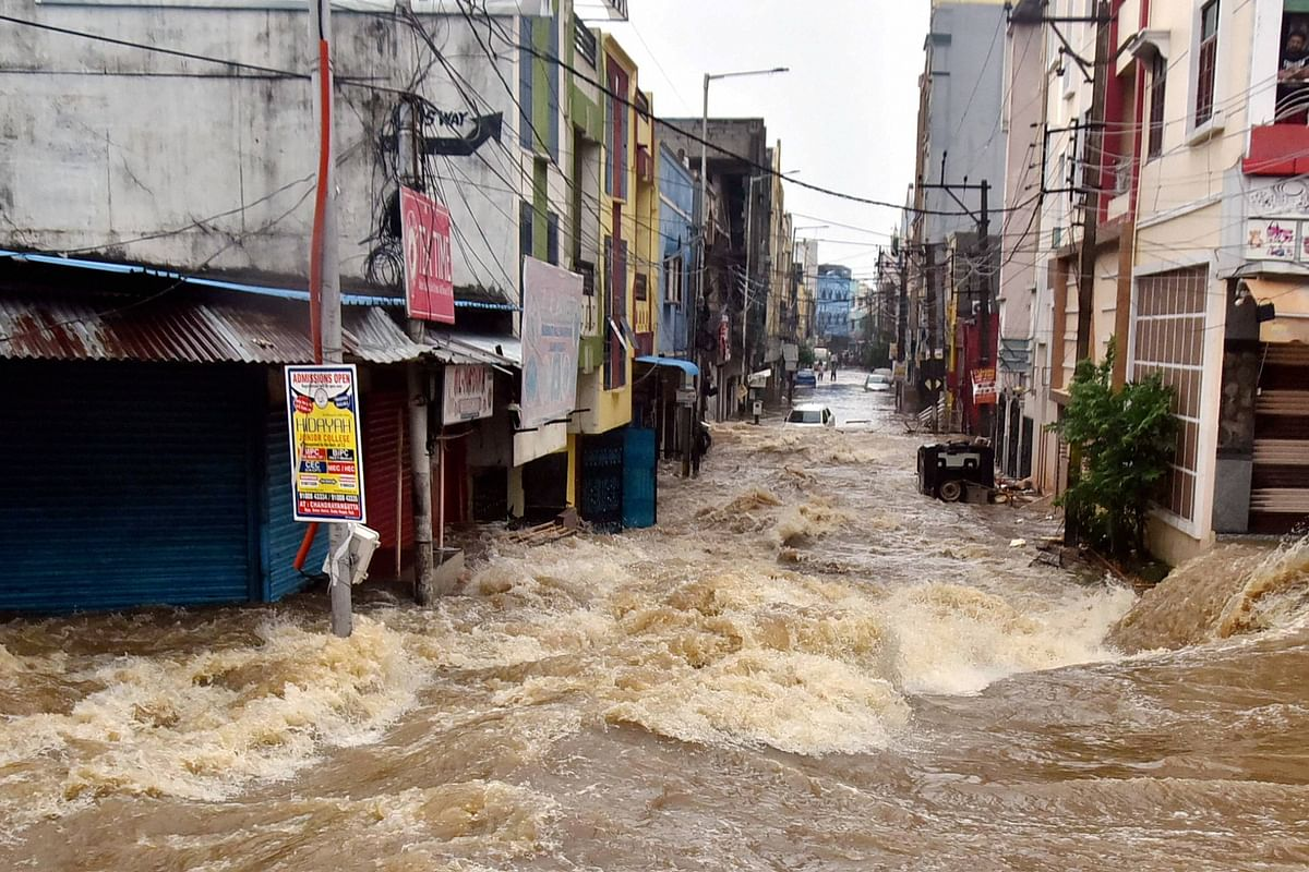 Floodwater gushes through a street following heavy rains, at Falaknuma, in Hyderabad, Wednesday, 14 October 2020.