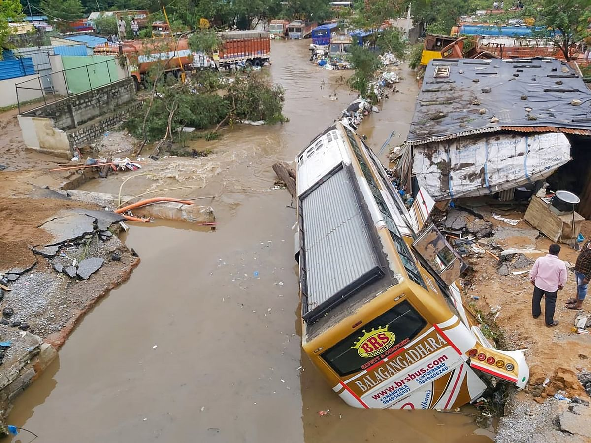 A bus damaged after a road caved-in following incessant rainfall across the state, at Gaganpahad-Shamshabad Road near Hyderabad, Wednesday, Oct. 14, 2020.