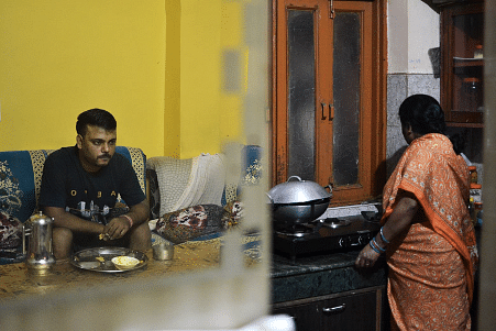 Ajay's worried reflection while his mother works in the kitchen.