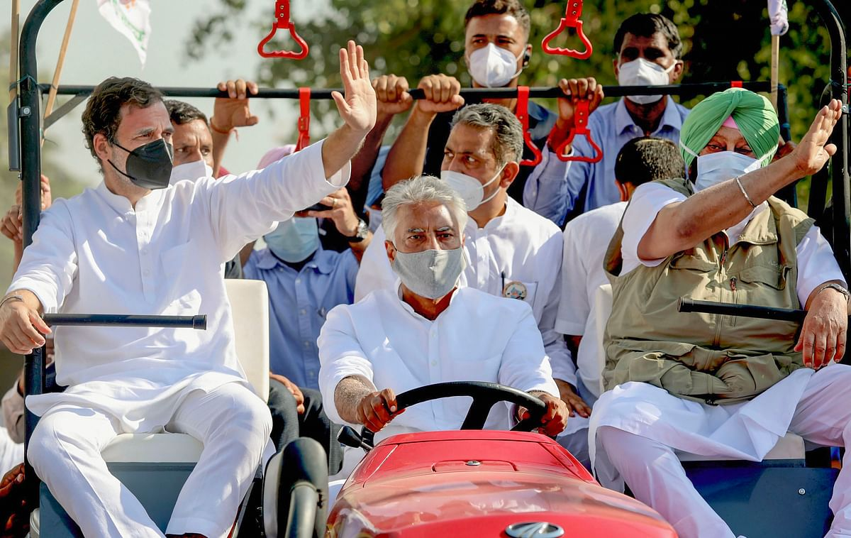 Former Congress President Rahul Gandhi and Punjab Chief Minister Capt. Amarinder Singh ride a tractor driven by PPCC President Sunil Kumar Jakhar during their Kheti Bachao Yatra over new farm laws, in Sangrur district.