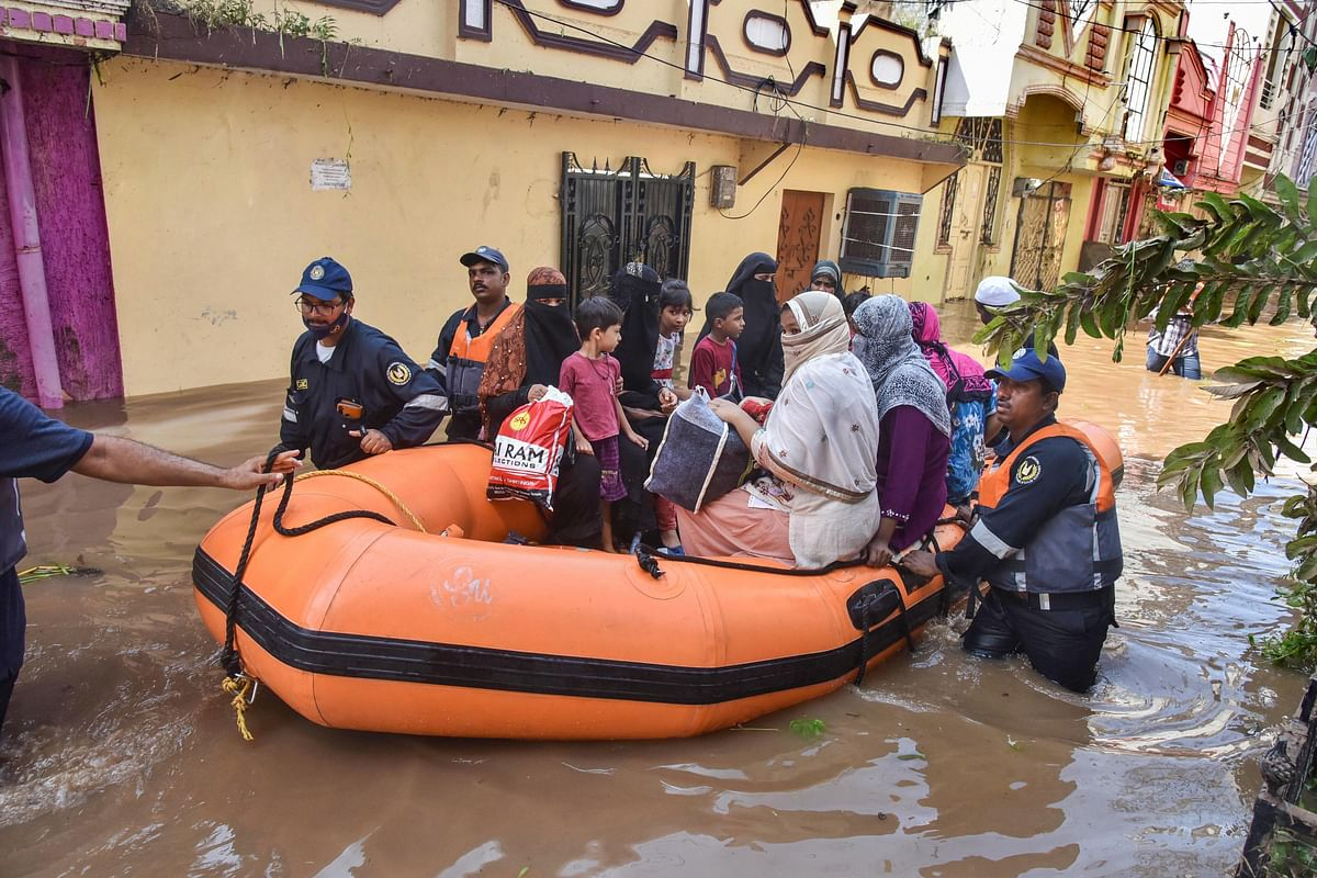 GHMC personnel carry out a rescue operation to move flood-affected people to a safer place following heavy rains, at Hafiz Baba Nagar in Hyderabad,