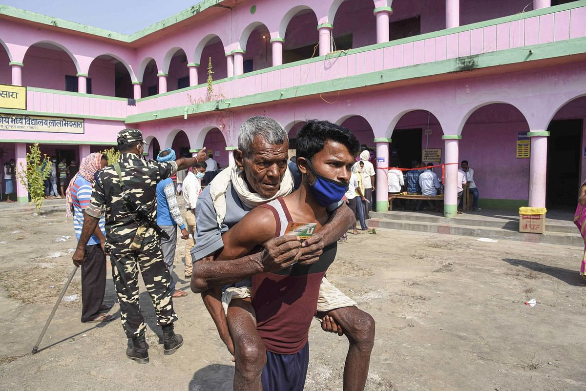 A young man carrying his father leaves after they cast their votes for the first phase of Bihar Assembly Elections, at Paliganj constituency in Patna, Wednesday, 28 October.