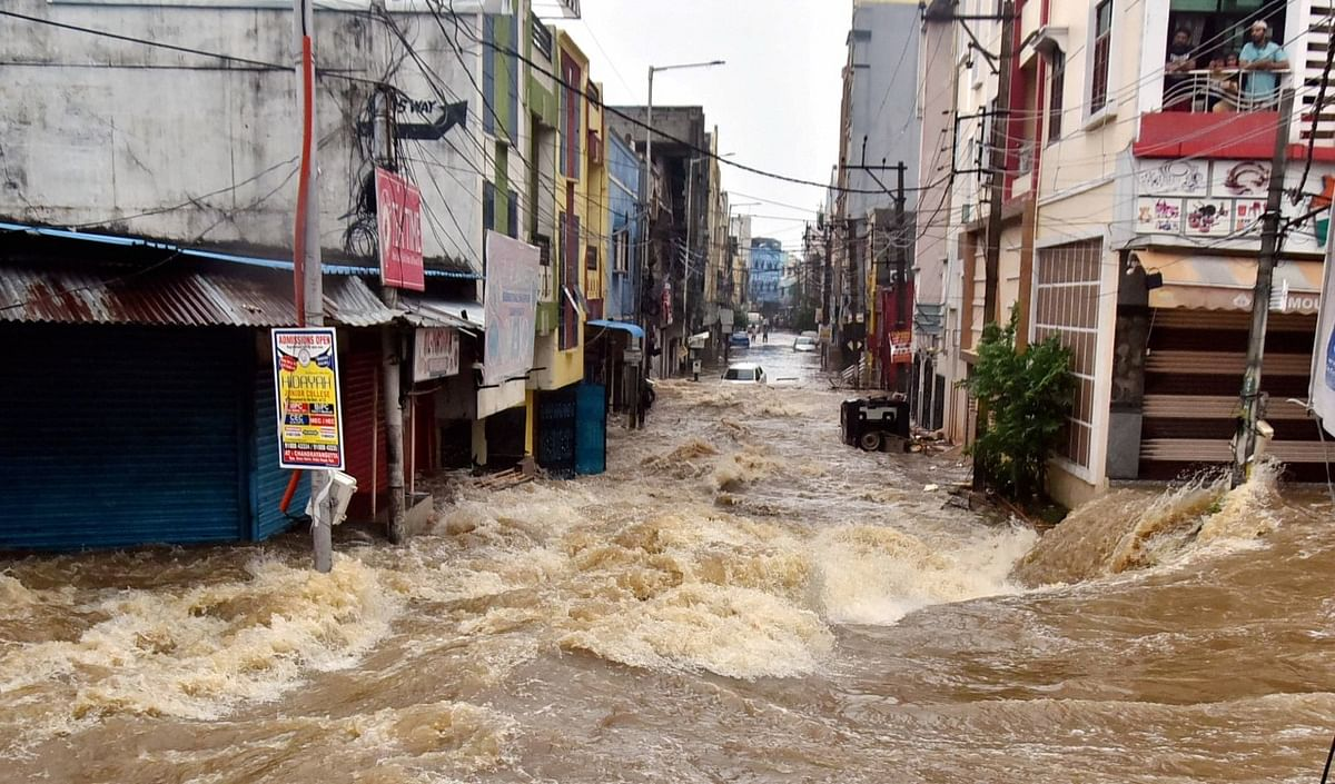 Floodwater gushes through a street following heavy rains, at Falaknuma, in Hyderabad, Wednesday, Oct. 14, 2020.