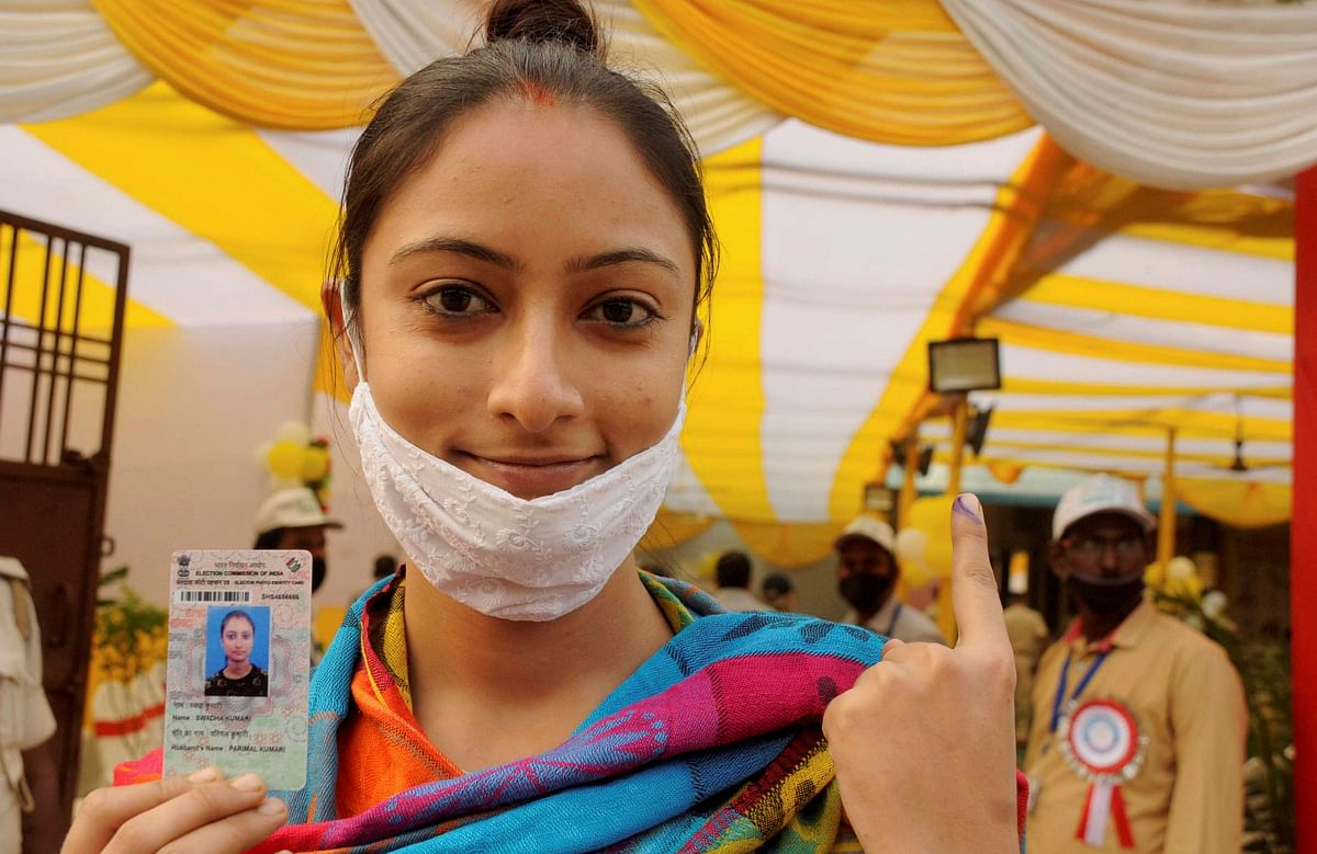 A woman shows an ID and her finger marked with indelible ink after casting vote during the second phase of Bihar assembly polls, amid the ongoing coronavirus pandemic, in Patna district.