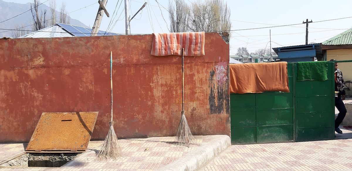 Brooms & an open manhole at the entrance of Sheikh Colony, Batwara, Srinagar.