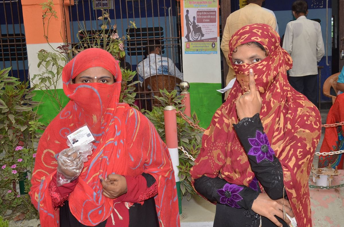 Women show ID and fingers marked with indelible ink after casting vote during the second phase of Bihar assembly polls, amid the ongoing coronavirus pandemic, in Muzaffarpur district.
