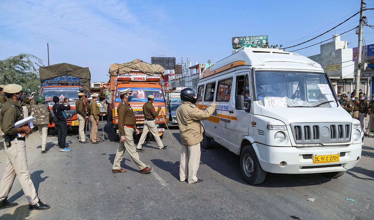 Police personnel check vehicles as the security is enhanced at Singhu border in view of the Delhi Chalo protest march by farmers against the new farm laws, in New Delhi