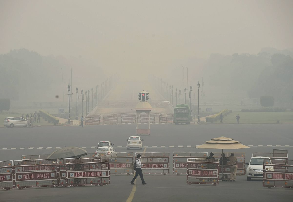 A man crosses a road at Rajpath in the backdrop of an atmosphere shrouded in smog, in New Delhi.