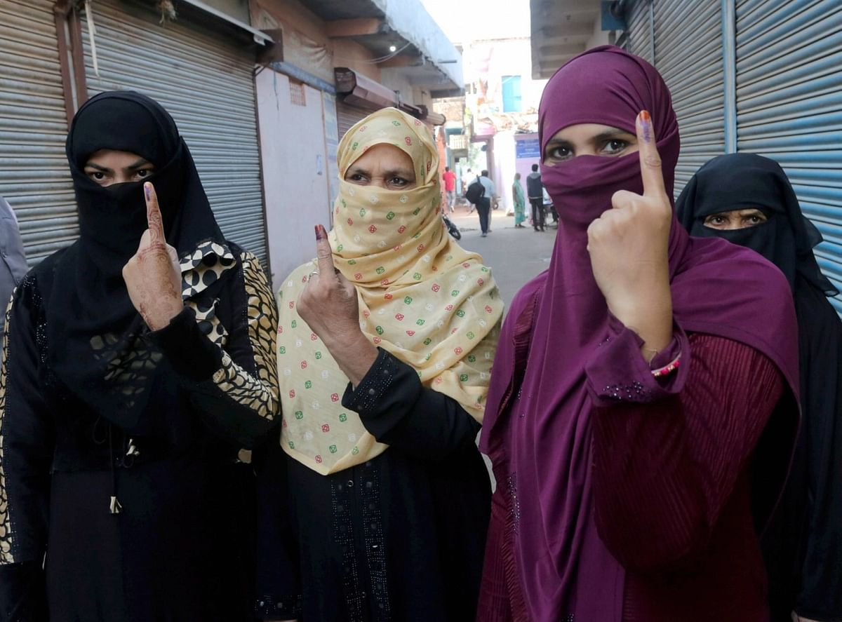 Women show their fingers marked with indelible ink after casting vote during the Madhya Pradesh Assembly bypolls, amid the ongoing coronavirus pandemic, in Raisen district, Tuesday, 3 November.