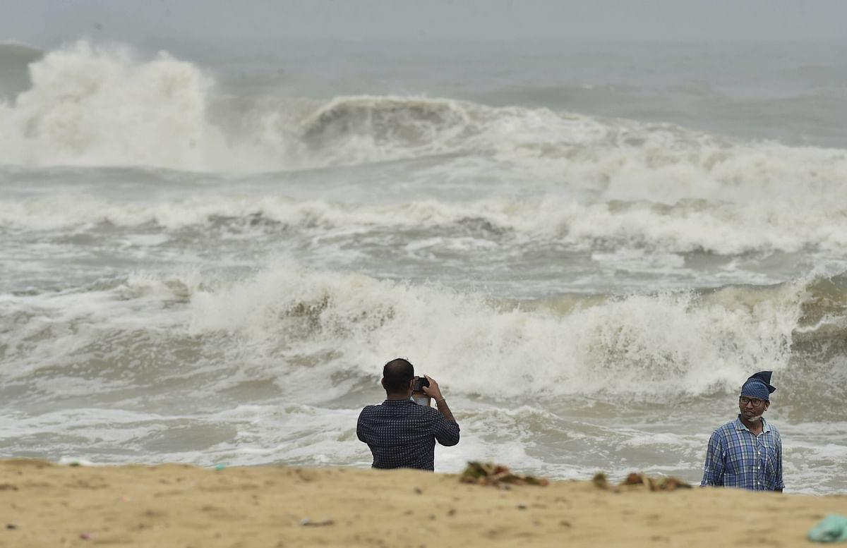 A man clicks photographs as turbulent waves crash the shore before the landfall of Cyclone Nivar, at Marina Beach in Chennai, Tuesday, Nov. 24.