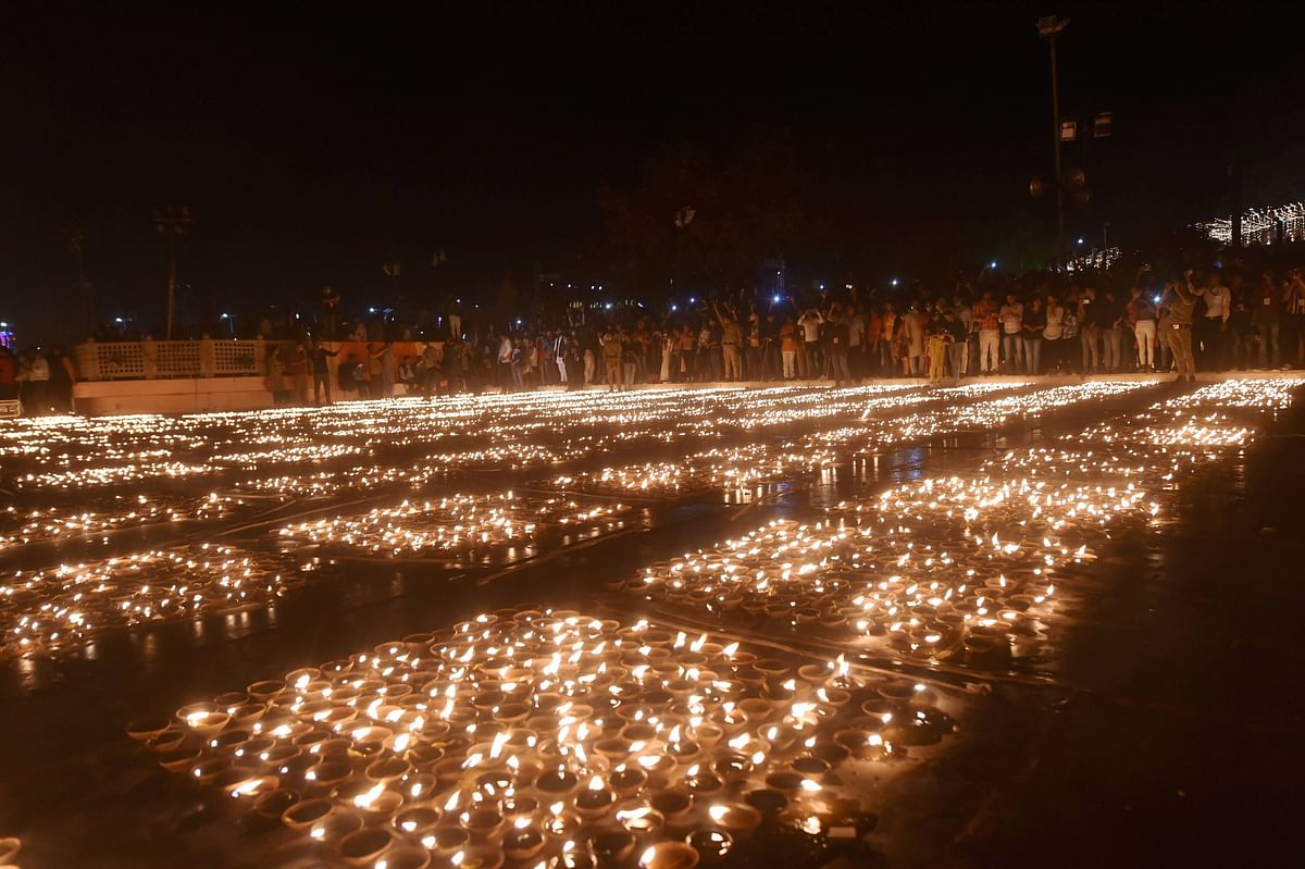 Devotees light earthen lamps on the bank of Saryu River during Deepotsav celebrations in Ayodhya, Friday, 13 November.