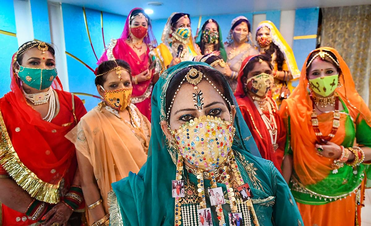 Women wearing designer masks pose for photographs as they prepare to celebrate Karwa Chauth festival in Bhopal.