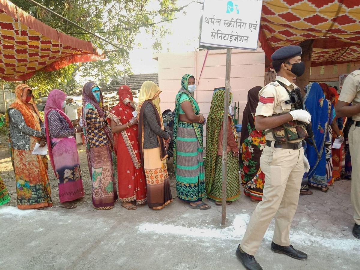 Women stand in a queue to cast their votes during the Madhya Pradesh Assembly bypolls, amid the ongoing coronavirus pandemic, in Indore district, Tuesday, 3 November.
