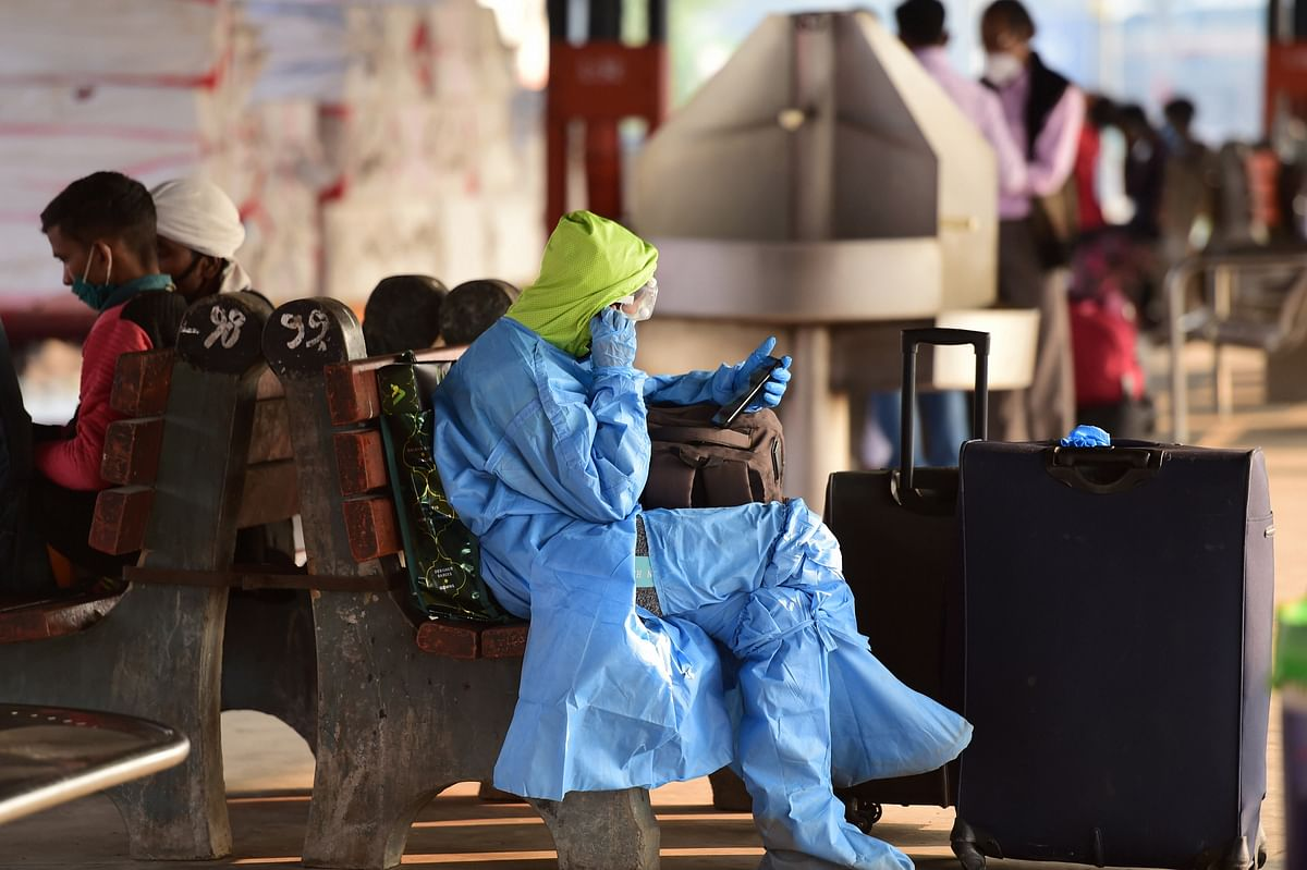 A woman passenger wearing protective suit, waits for train at New Delhi station.