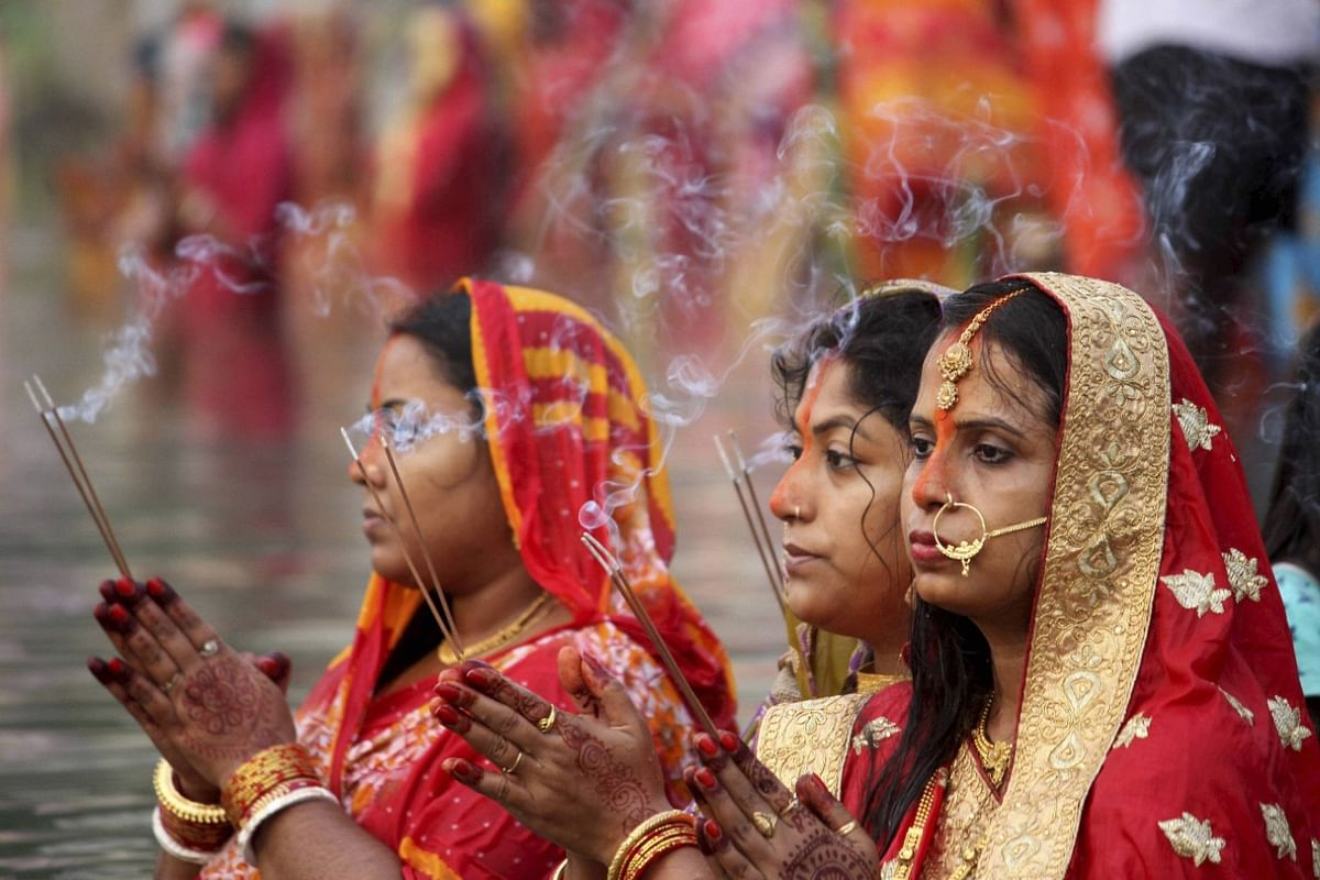 Devotees pray to the Sun God in a pond on the occasion of Chhath Puja in Agartala.