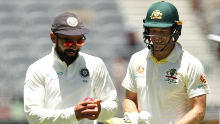 Virat Kohli and Tim Paine share a light moment.