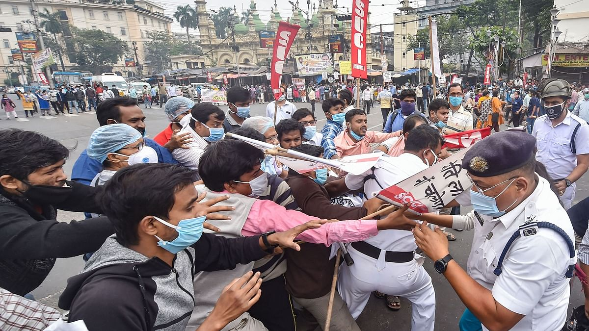 Police personnel detain protestors as they block a road during a protest in support of the nationwide strike by ten central trade unions against various policies of the NDA government, in Kolkata, Thursday, Nov. 26, 2020.