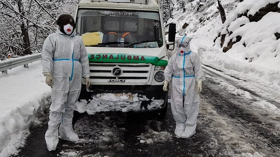 Pilot Manoj and EMT Jay Lalita captured with the ambulance they pushed through 45cm snow on Monday.