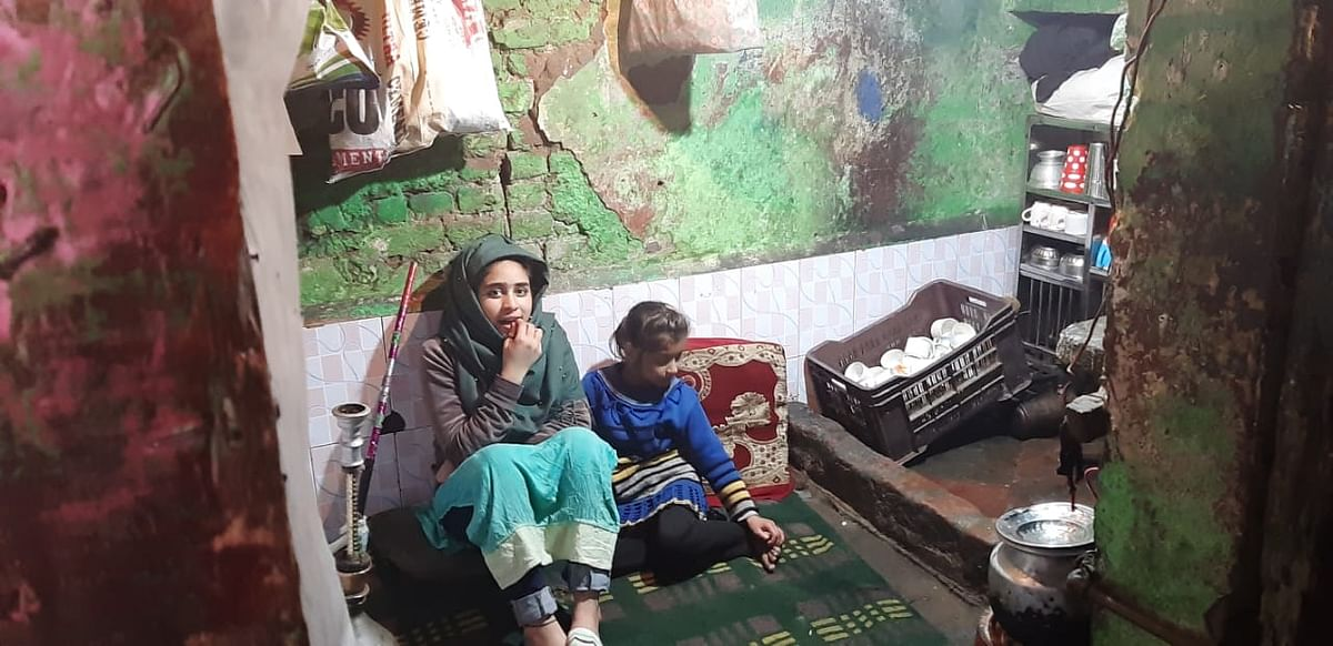 Young girls sitting inside their one-room shack in Zahid Pora, Srinagar.