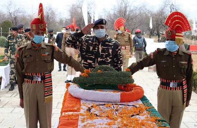 Border Security Force (BSF) officer lays wreath on the coffin of their colleague, who was killed in a ceasefire violation at the Line of Control (LoC) in Kashmir during a wreath laying ceremony in Humhama, on the outskirts of Srinagar, November 15, 2020.