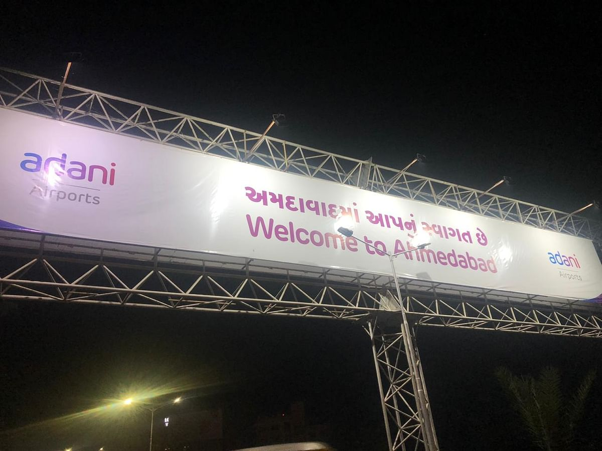 The hoarding shows 'Welcome to Ahmedabad' while exiting the airport.