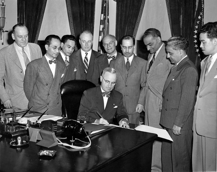 President Truman signing the Immigration bill with JJ Singh (third from right)