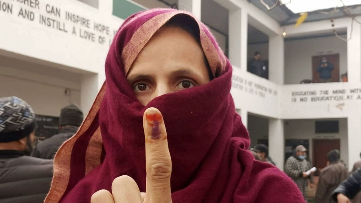 A woman shows her ink-marked finger after casting her vote during the third phase of the DDC elections, at a polling station in Ganderbal area of central Kashmir, on Friday, 4 December 2020.