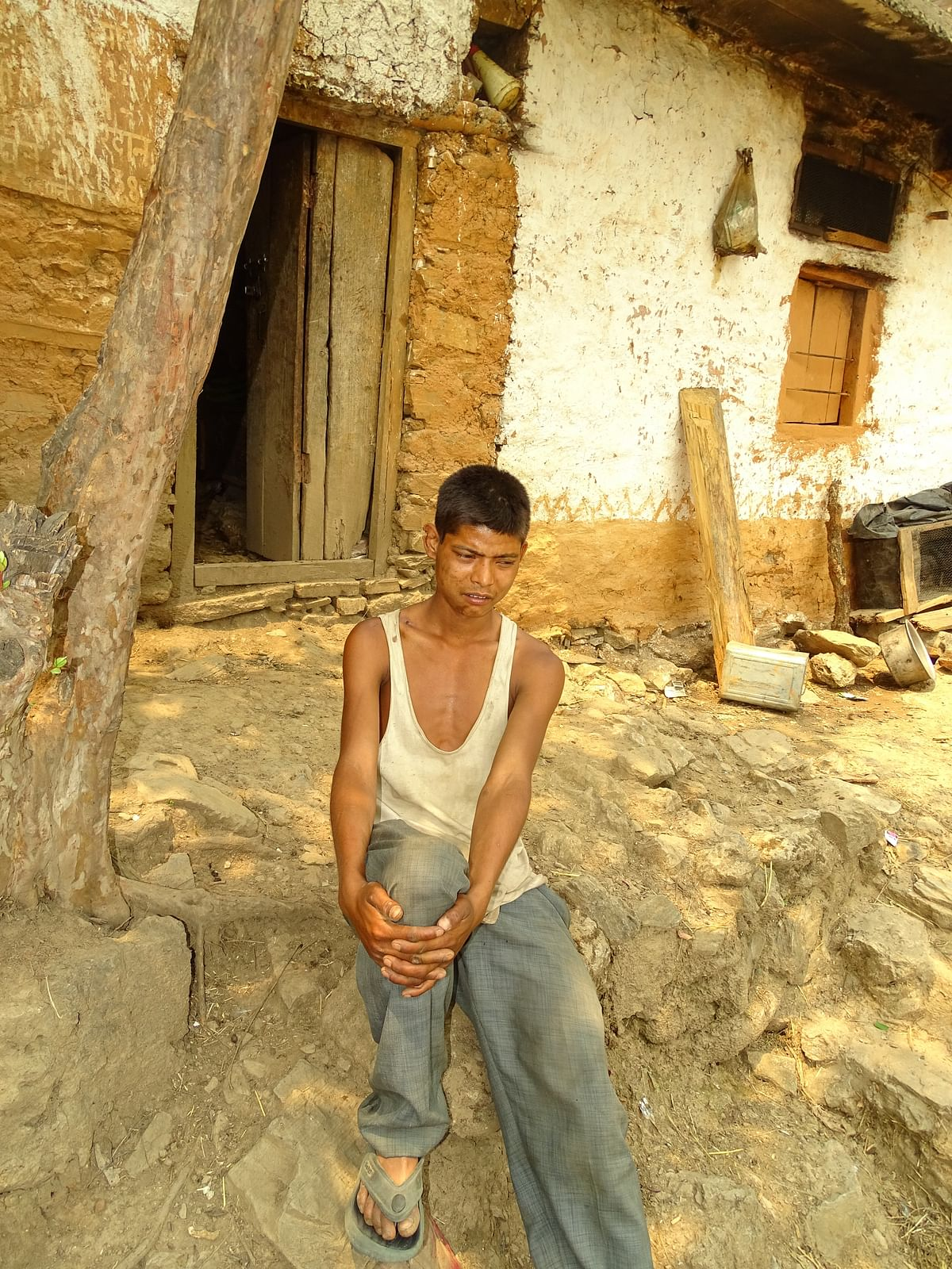 A young Raji lad in front of his poorly earth-plastered house.
