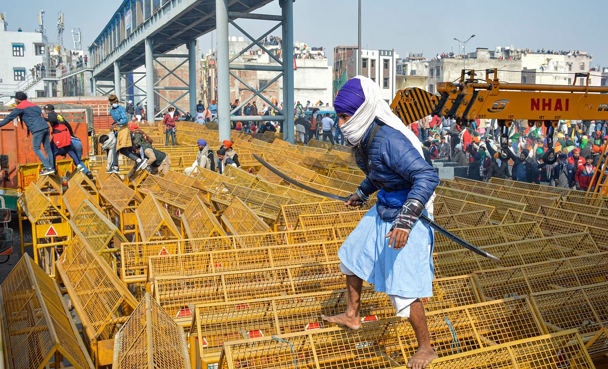 A farmer walks over the police barricades set up on a road at Akshardham to stop farmers during their during the Kisan Gantantra Parade amid the 72nd Republic Day celebrations, in New Delhi, Tuesday, 26 January 2021.