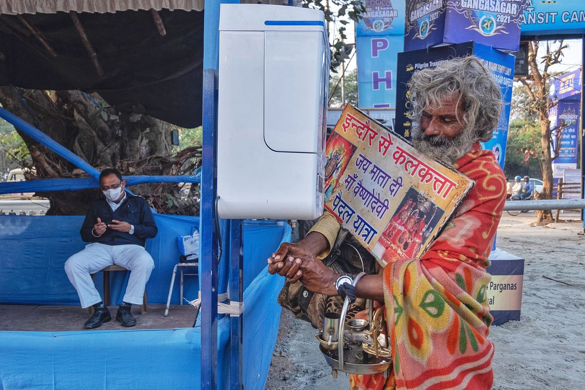 <i>Sadhus and d</i>evotees sanitize their hands at the entrance.