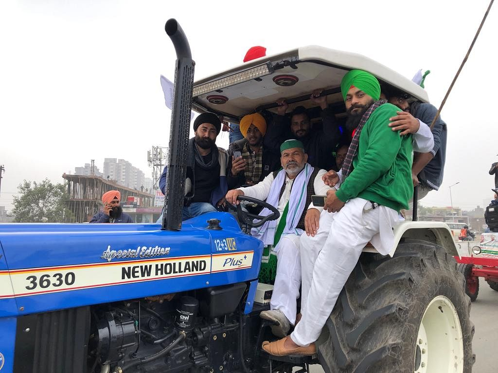 Rakesh Tikait (in the driver's seat) participates in the tractor rally.