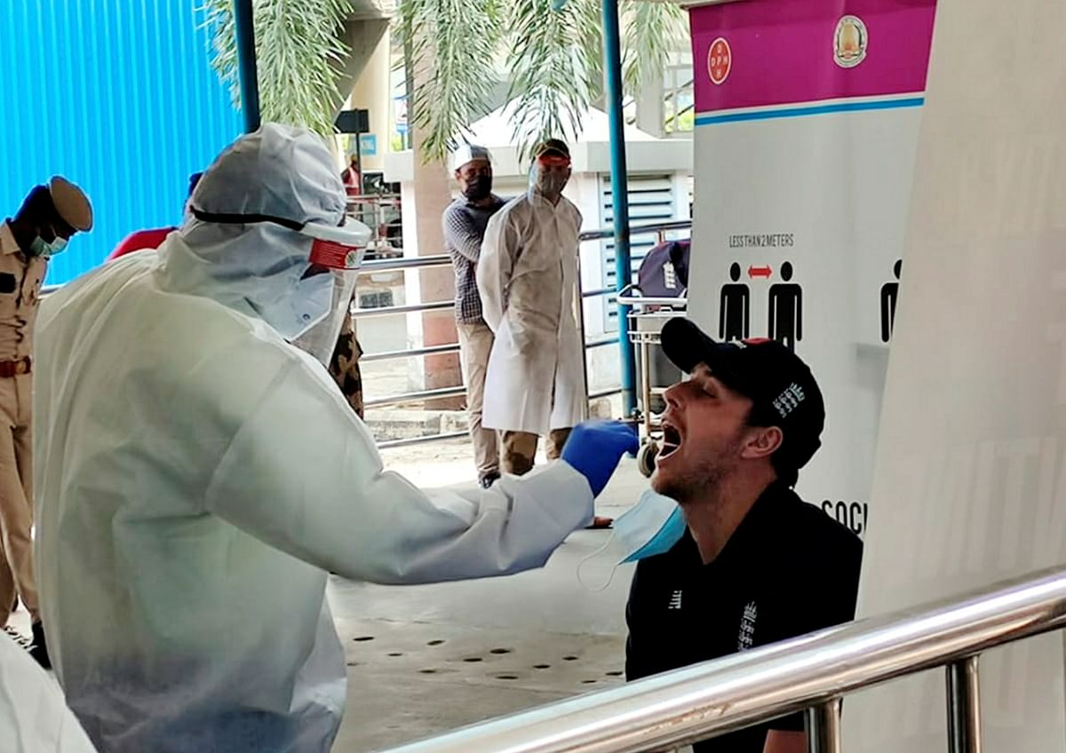 A player of England cricket team gives his swab sample to a medic for COVID-19 test as he arrives at the airport ahead of the test series against India, in Chennai, Wednesday, 27 January 2021.