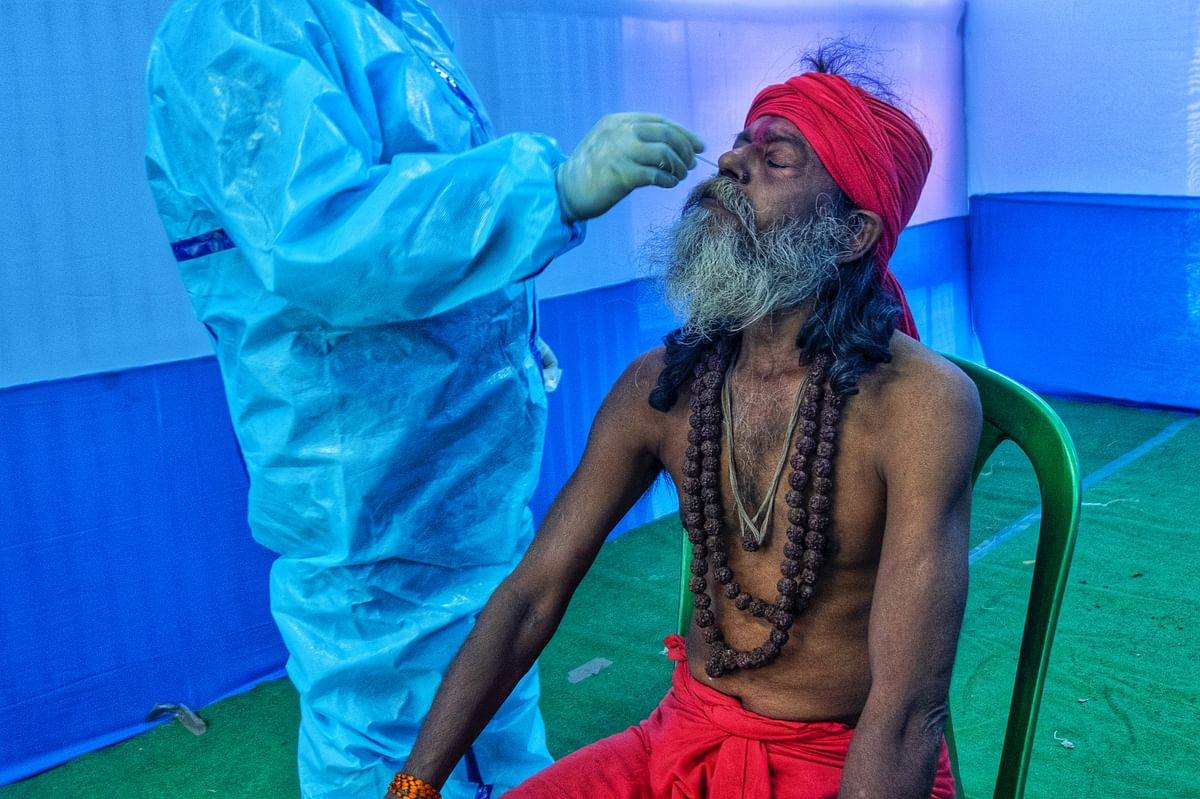 A healthcare worker collecting the swab sample of a devotee.