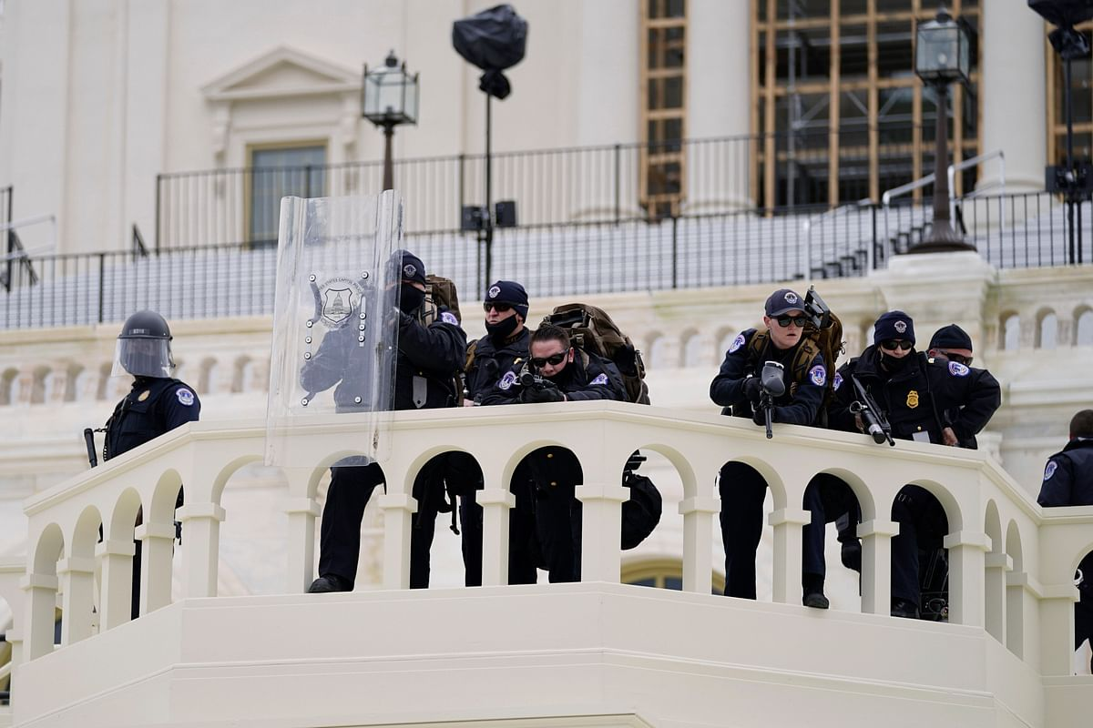 Police keep a watch on demonstrators who tried to break through a police barrier on Wednesday, 6 January, towards the Capitol in Washington, DC.