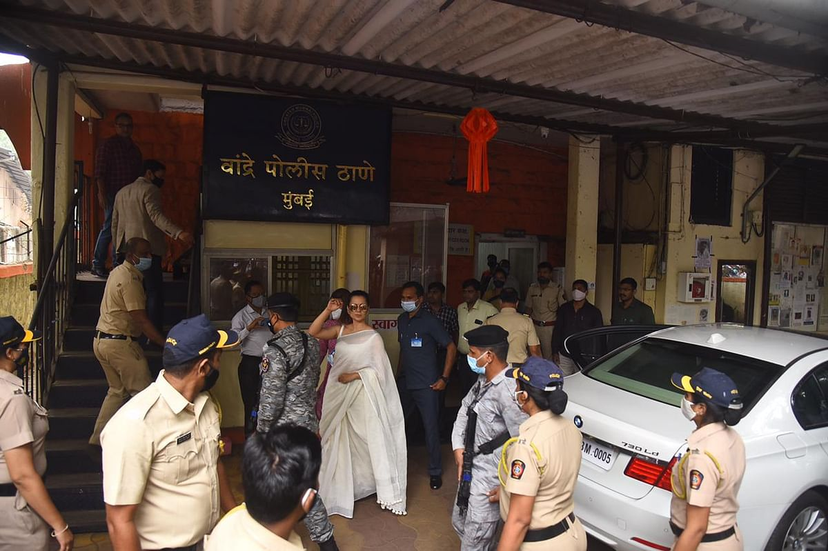 Kangana Ranaut waves to the cameras before entering the police station.