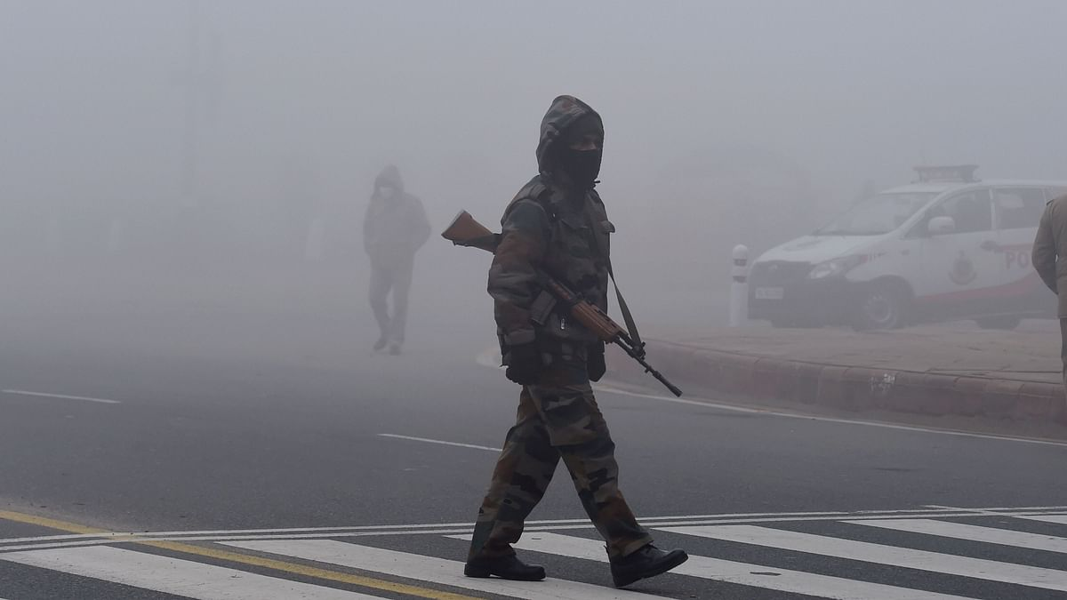 A security personnel walks across a road during the rehearsals for Republic Day Parade amid dense fog at Rajpath, in New Delhi, Saturday, 16 January 2021.