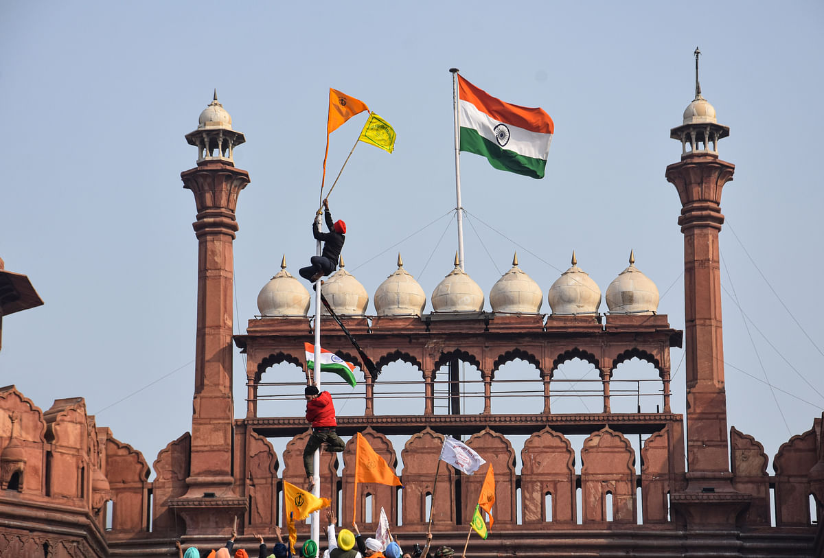 Farmers hoist flags at the Red Fort during the Kisan Gantantra Parade amid the 72nd Republic Day celebrations, in New Delhi, Tuesday, 26 January 2021.