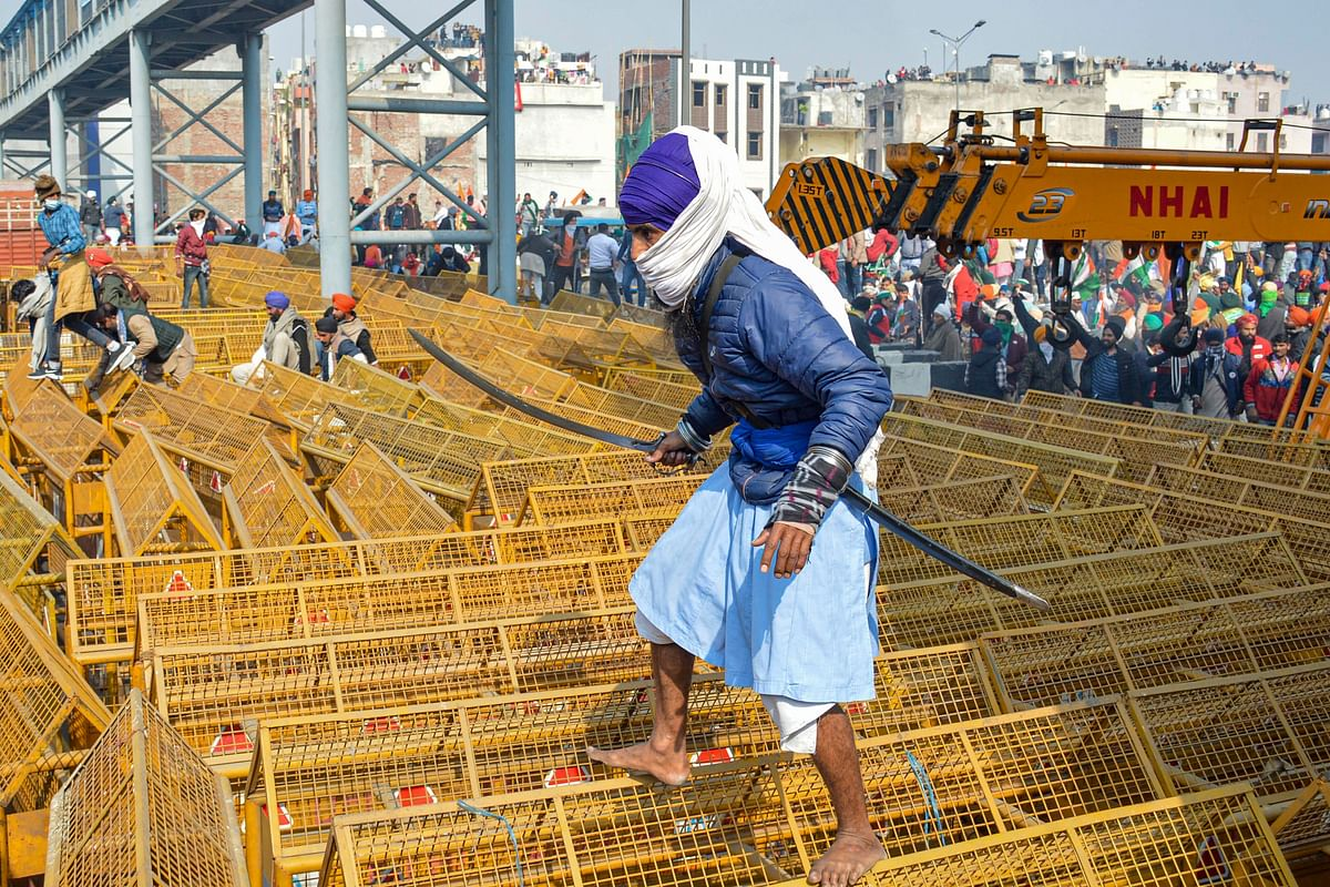 A farmer walks over the police barricades set up on a road at Akshardham to stop farmers during their during the Kisan Gantantra Parade amid the 72nd Republic Day celebrations.