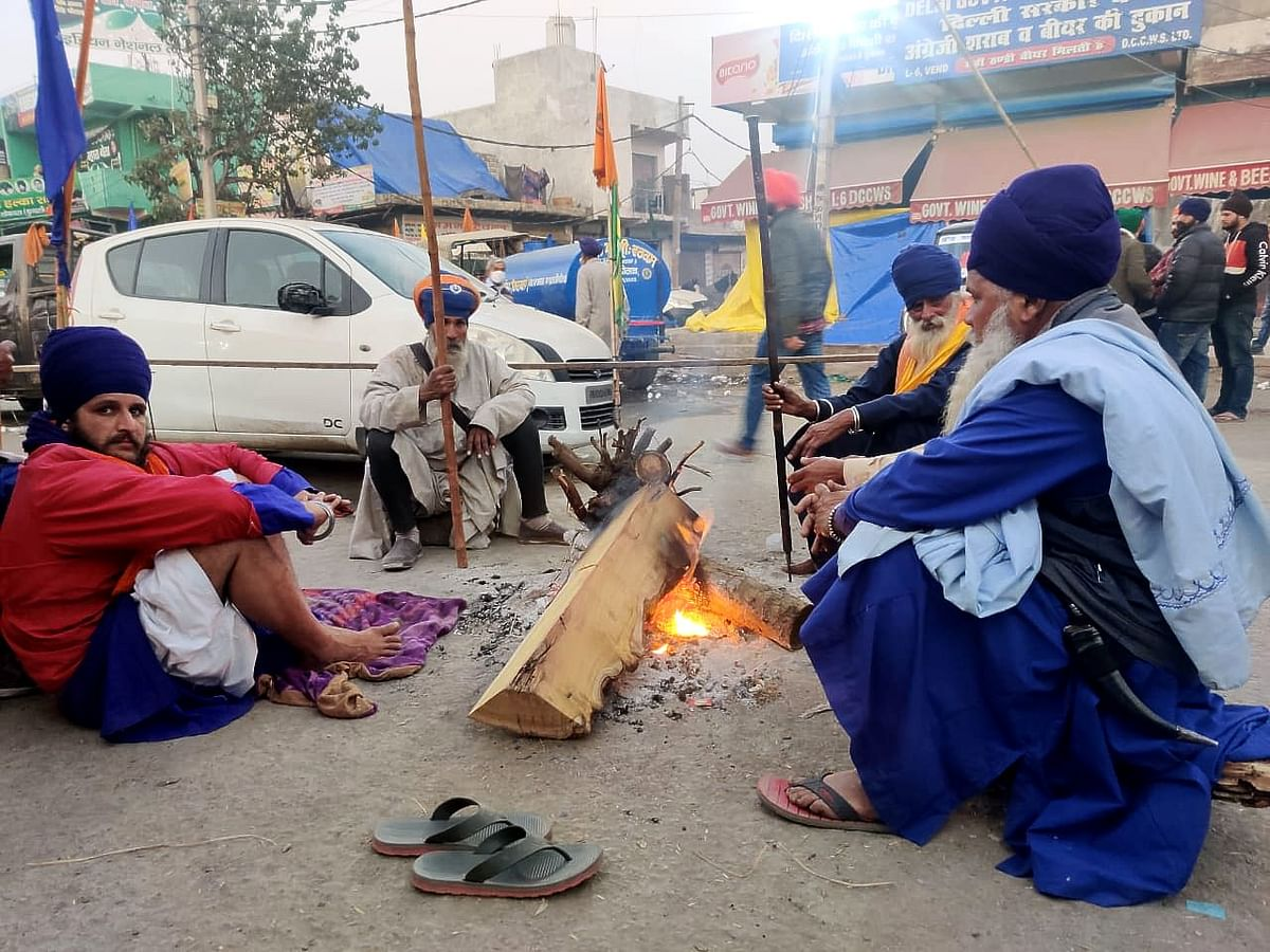 Farmers gather around fire as evening set at Singhu, a day after Republic Day violence.