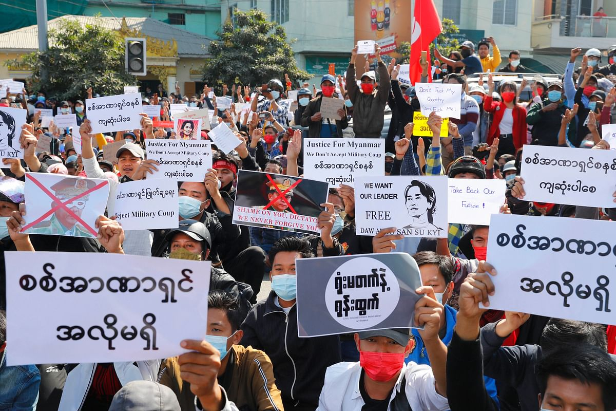 "Protesters display placards with a defaced image of Myanmar military Commander-in-Chief Senior Gen. Min Aung Hlaing and calling for the release of detained Myanmar State Counselor Aung San Suu Kyi during a protest in Mandalay, Myanmar, Tuesday, Feb. 9, 2021. Protesters continued to gather Tuesday morning in major cities breaching Myanmars new military rulers ban of public gathering of five or more issued on Monday intended to crack down on peaceful public protests opposing their takeover. Placards in the front read as"" No dictatorship."""